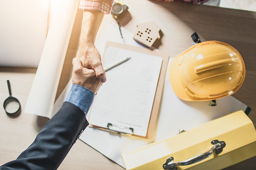 912867216 istock photo Top view of engineer and businessman shake hands on working table at working site 1006563046