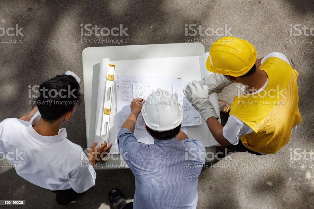 Draufsicht des Engineering-Team von Bauleiter, junge Außendiensttechniker und Vorarbeiter aussehen Papierplans auf Baustelle, Konzept für Teamarbeit – Foto