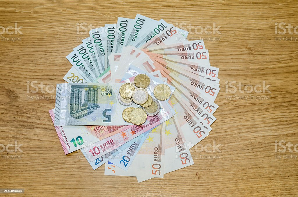 Top view of Euro coins and banknotes  on wooden table stock photo