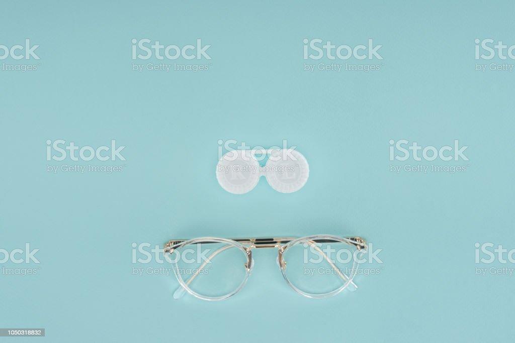 Draufsicht der Brillen und Kontaktlinsen Behälter auf blauem Hintergrund – Foto