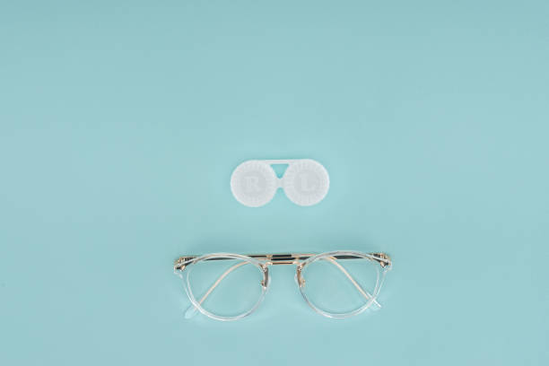 top view of eyeglasses and contact lenses container on blue background - contacts imagens e fotografias de stock