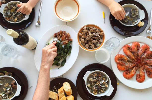 top view of family eating seafood around a white table from high view angle - spanish food stock photos and pictures