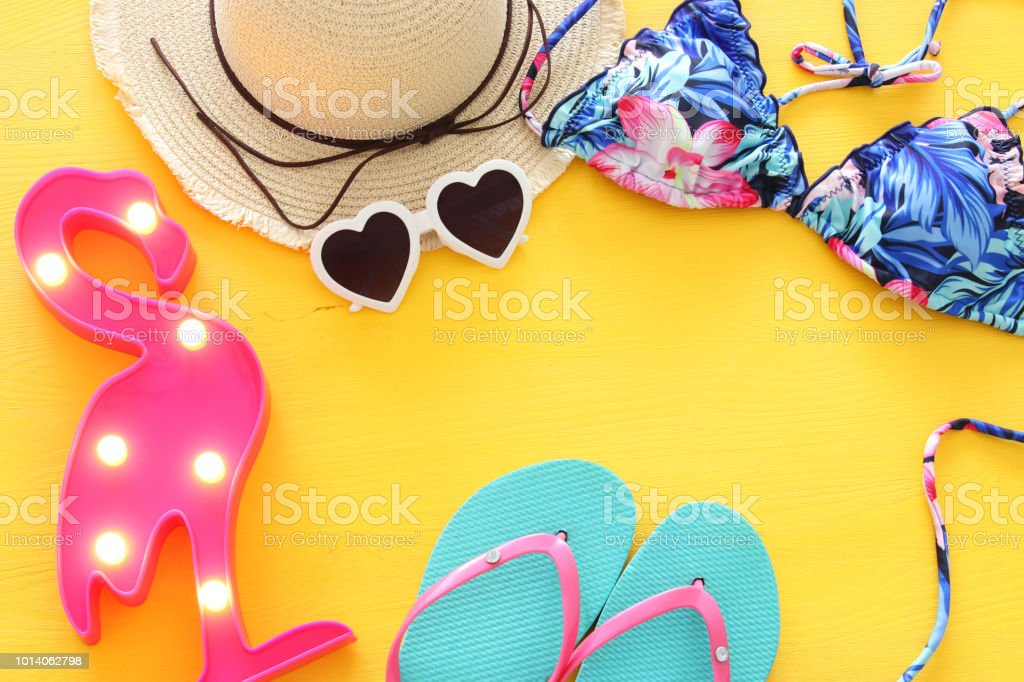 4fff7cf903 Top view of fashion female swimsuit bikini and white fedora hat over yellow wooden  background. Summer beach vacation concept. - Stock image .