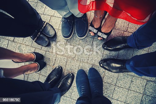 Top view of feet of fashionable, stylish people standing in a circle.