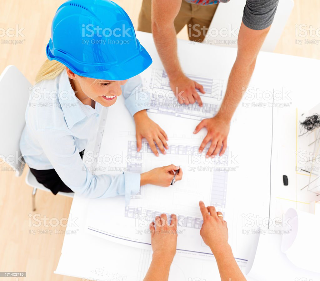 Top view of female architect with colleagues working on blue prints royalty-free stock photo