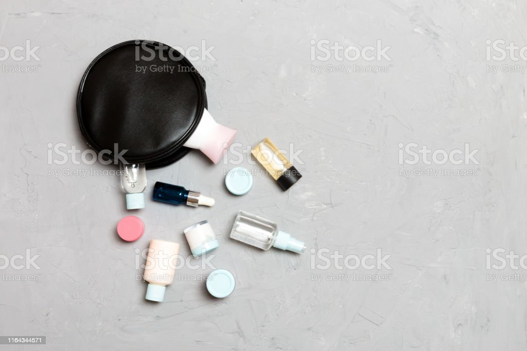Top view of female cosmetics bag with dropped out cosmetic products...
