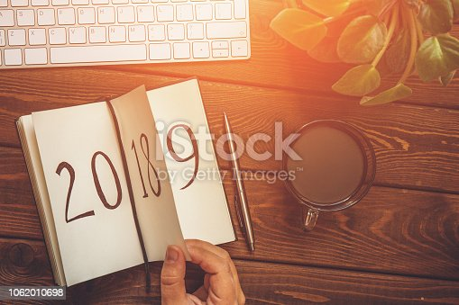 istock Top view of female hand flips notepad sheet on wooden table. 2018 is turning, 2019 is opening, toned 1062010698