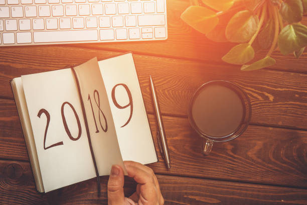 Top view of female hand flips notepad sheet on wooden table. 2018 is turning, 2019 is opening, toned Top view of female hand flips notepad sheet on wooden table. 2018 is turning, 2019 is opening, toned with light effect 2018 stock pictures, royalty-free photos & images