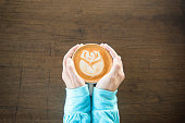 Top view of female hand holding hot coffee latte art rose foam in symbol of love in valentine festival on wooden table at coffee shop