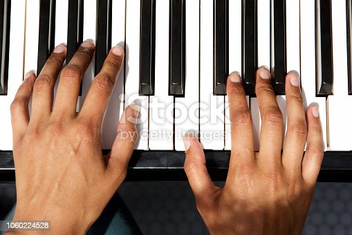 Close up top view of female hands playing piano