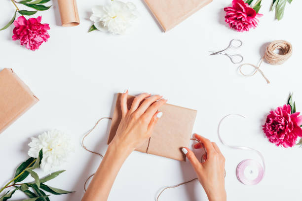 Top view of female hands wrapping presents stock photo