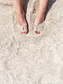 Top view of female legs with red pedicure in the beach sand. Rest and recreation at sea. Copy space. High quality photo. Flat lay.