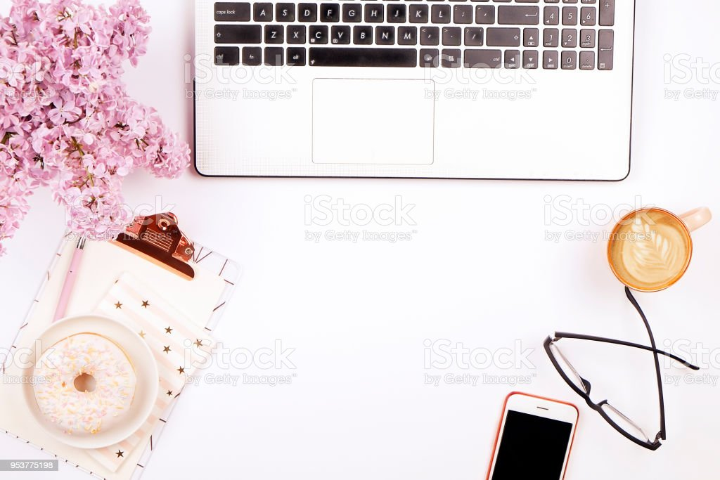 Top View Of Female Worker Desktop With Laptop, Flowers And Different Office  Supplies Items.