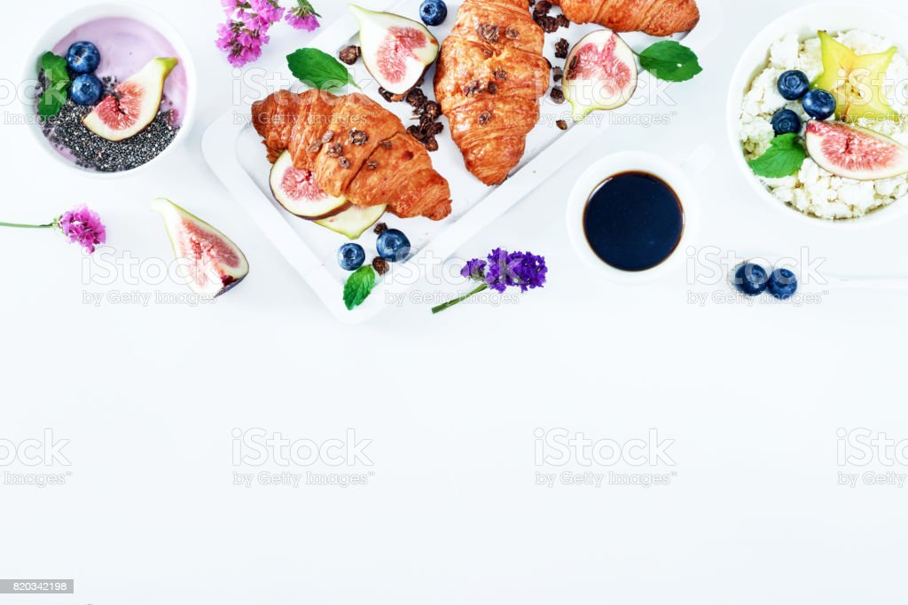 Top view of feminine breakfast on a white table with empty space. stock photo