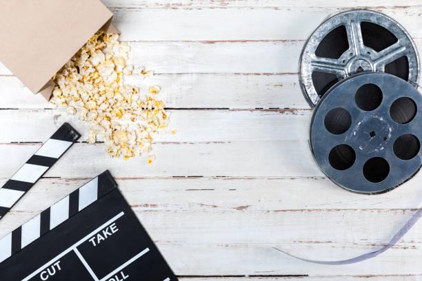 top view of film reels, popcorn and movie clapper on wooden table, movie time concept - biglietto del cinema foto e immagini stock