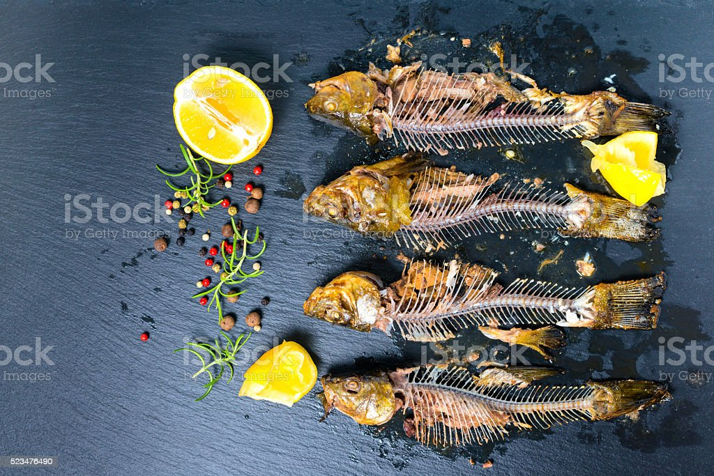 top view of fish skeleton bones, squeezed lemon and  peppers stock photo
