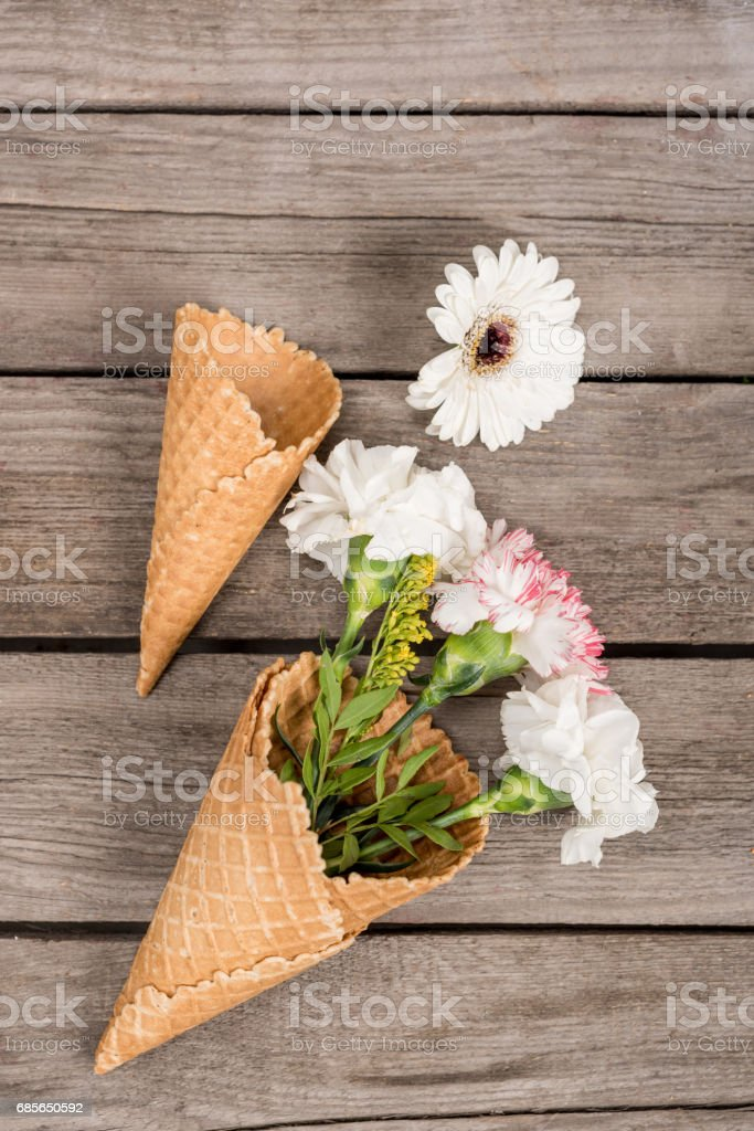 top view of flowers in sugar cones laying on wooden table, wooden background royalty-free stock photo