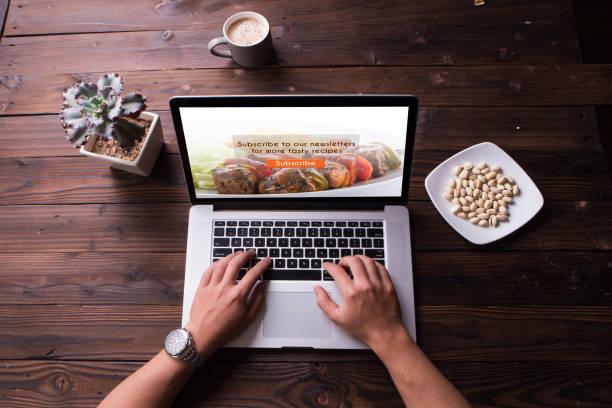 Top view of food blog subscription concept on the laptop / computer screen with wooden desk background stock photo