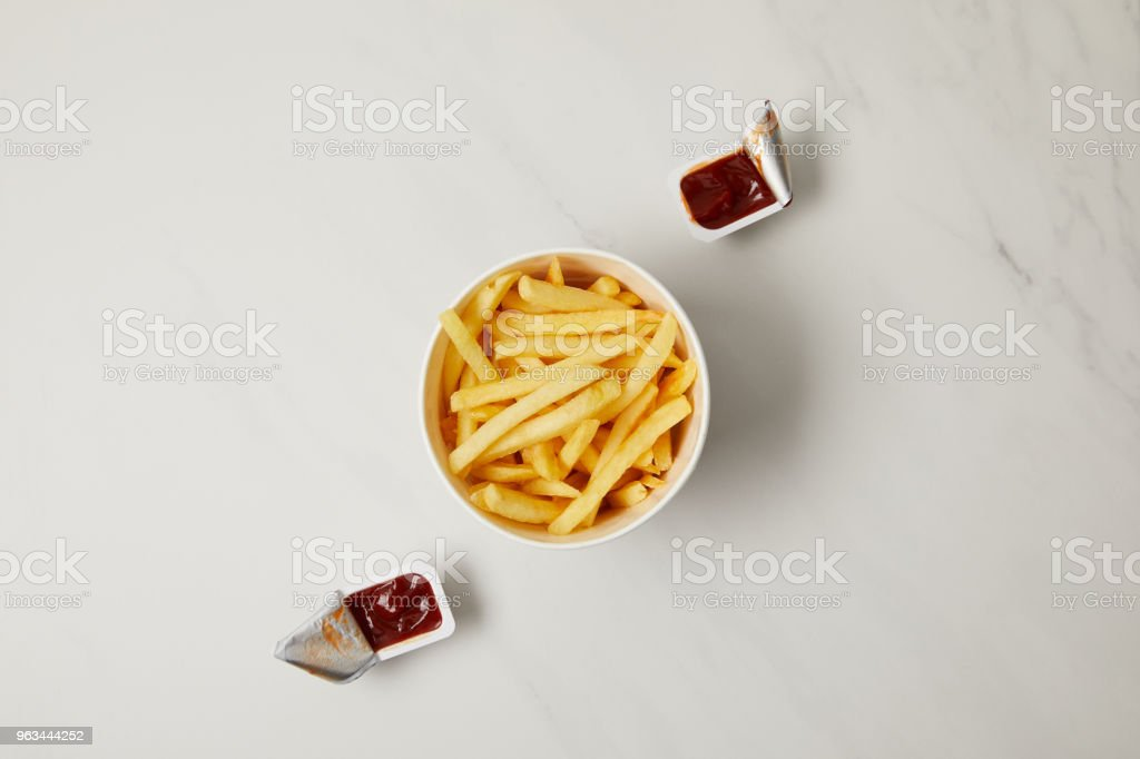 top view of french fries in bowl with containers of ketchup on white - Zbiór zdjęć royalty-free (Bez ludzi)