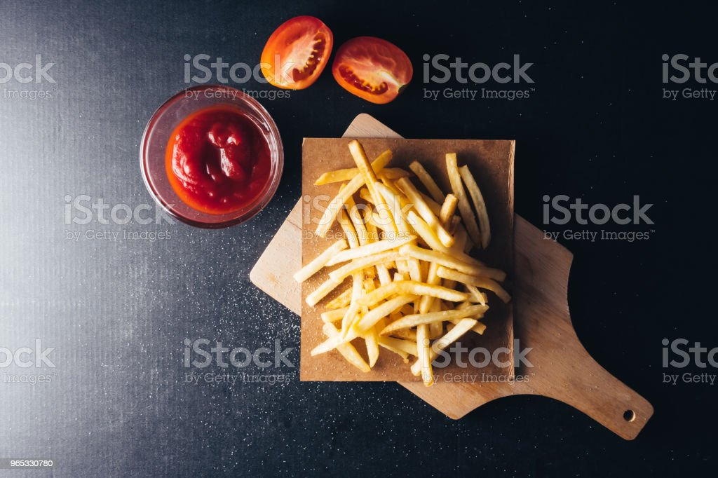 Top view of French fries with ketchup on black background royalty-free stock photo