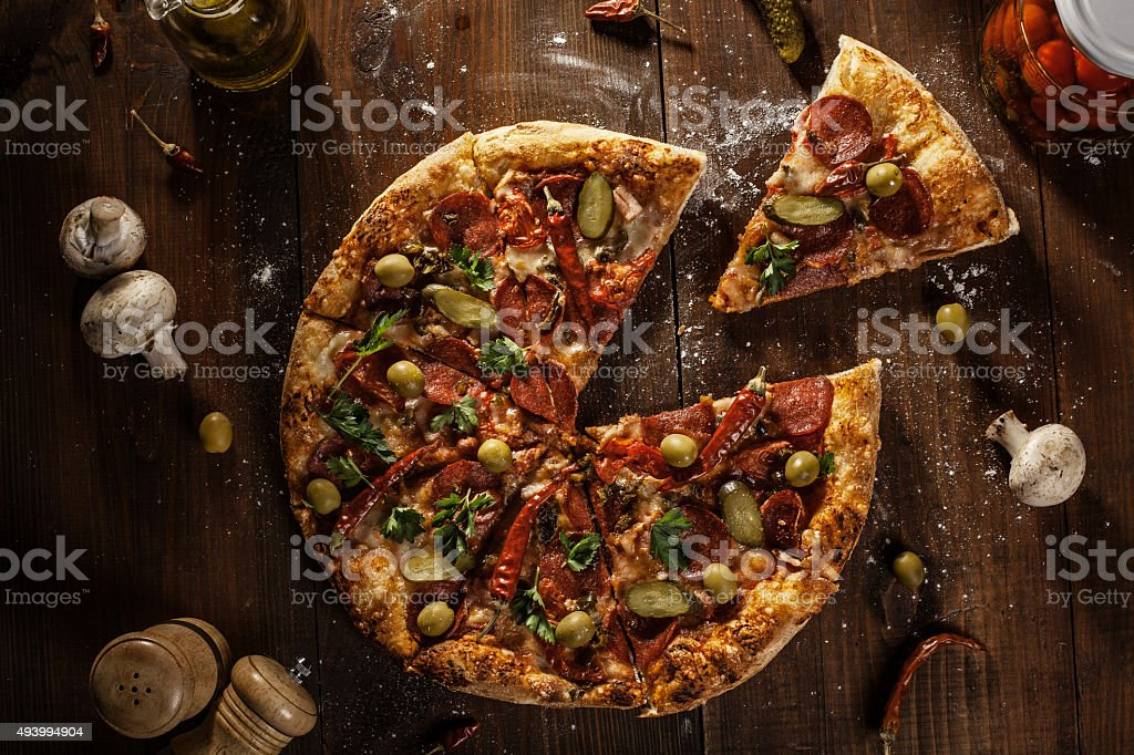 top view of fresh baked pizza with slice stock photo