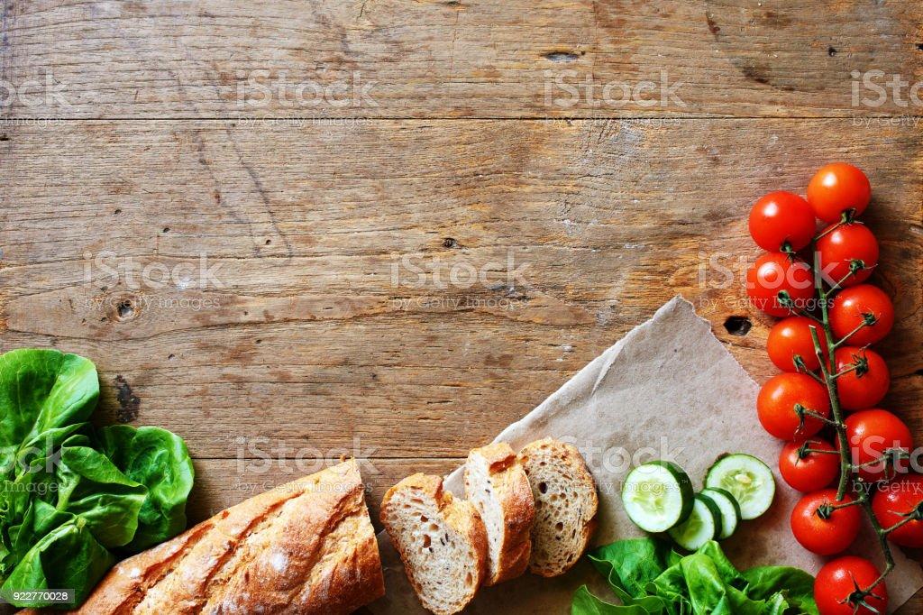 Draufsicht auf frischem Brot, Tomaten, Gurken und Salat auf Holztisch. – Foto