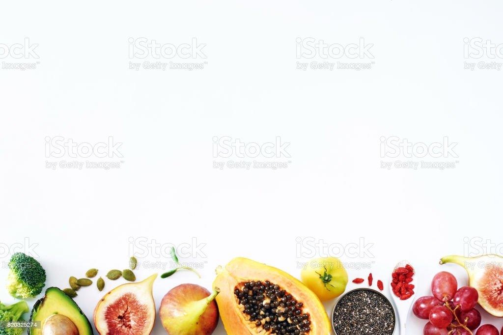 Draufsicht auf frisches Obst, Gemüse, Samen, Nüssen und Superfoods auf weiße Tafel mit dem leeren Raum. – Foto