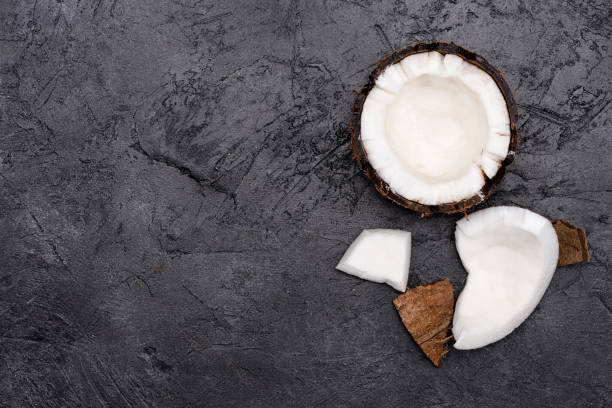 Top view of fresh healthy broken coconut on black background stock photo