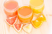 Top view of fresh juice in glass with pieces of various fruits on wooden background. Healthy vitamins background