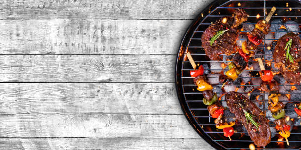 top view of fresh meat and vegetable on grill placed on wood - barbecue grill stock photos and pictures