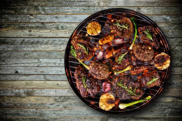 draufsicht von frischem fleisch und gemüse auf den grill gelegt auf holzboden - gitter stock-fotos und bilder