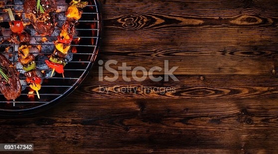 istock Top view of fresh meat and vegetable on grill placed on wooden floor 693147342