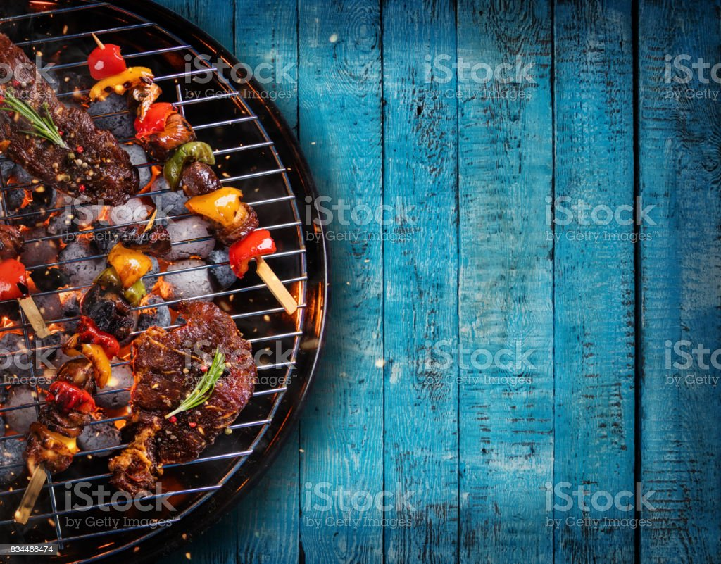 Top view of fresh meat and vegetable on grill placed on wooden planks stock photo