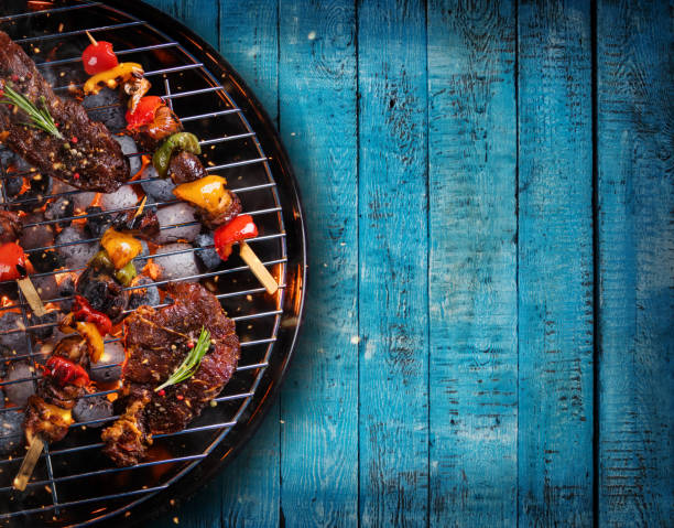 top view of fresh meat and vegetable on grill placed on wooden planks - barbecue grill stock photos and pictures