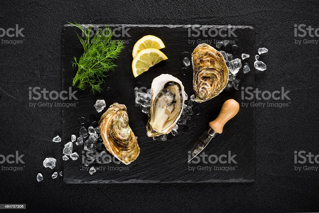 Top view of fresh oysters served on black stone stock photo