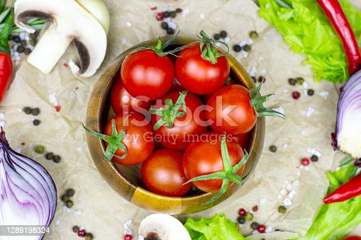 Top view of fresh red ripe cherry tomatoes in wooden bowl with salad leaves, onion, pepper, champignon mushrooms, spices and salt on light food background.