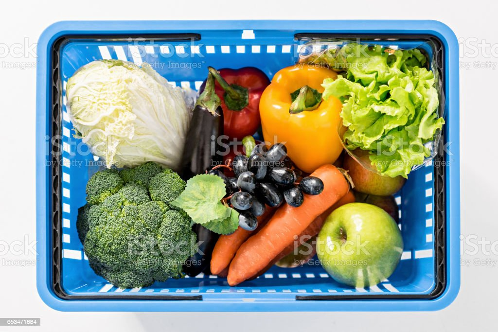 top view of fresh ripe vegetables in shopping basket on white stock photo