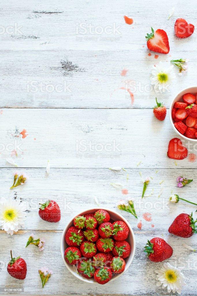 Draufsicht der frischen Erdbeere in Schüssel mit Blumen auf weißen Tisch mit textfreiraum geschmückt. – Foto