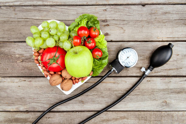 top view of fresh various vegetables, fruits and blood pressure gauge on wooden surface, healthy eating concept stock photo