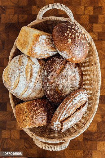 istock Top view of Freshly and warm baked bread rolls in the basket on wooden table. Made by artisan. 1067046998
