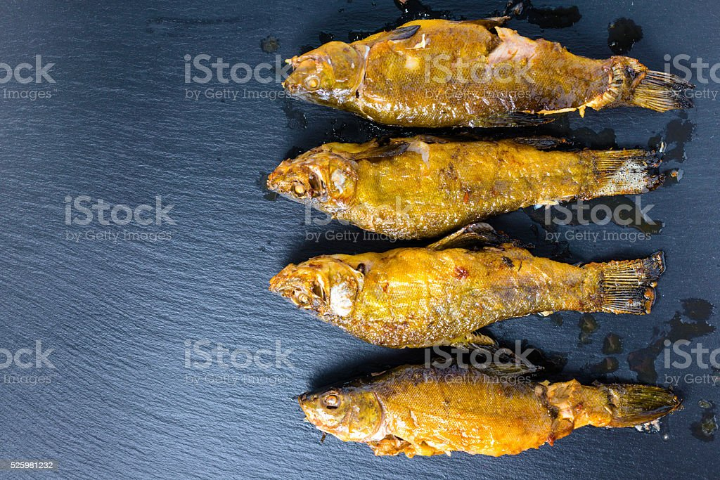 top view of fried tench fish served on slate background stock photo