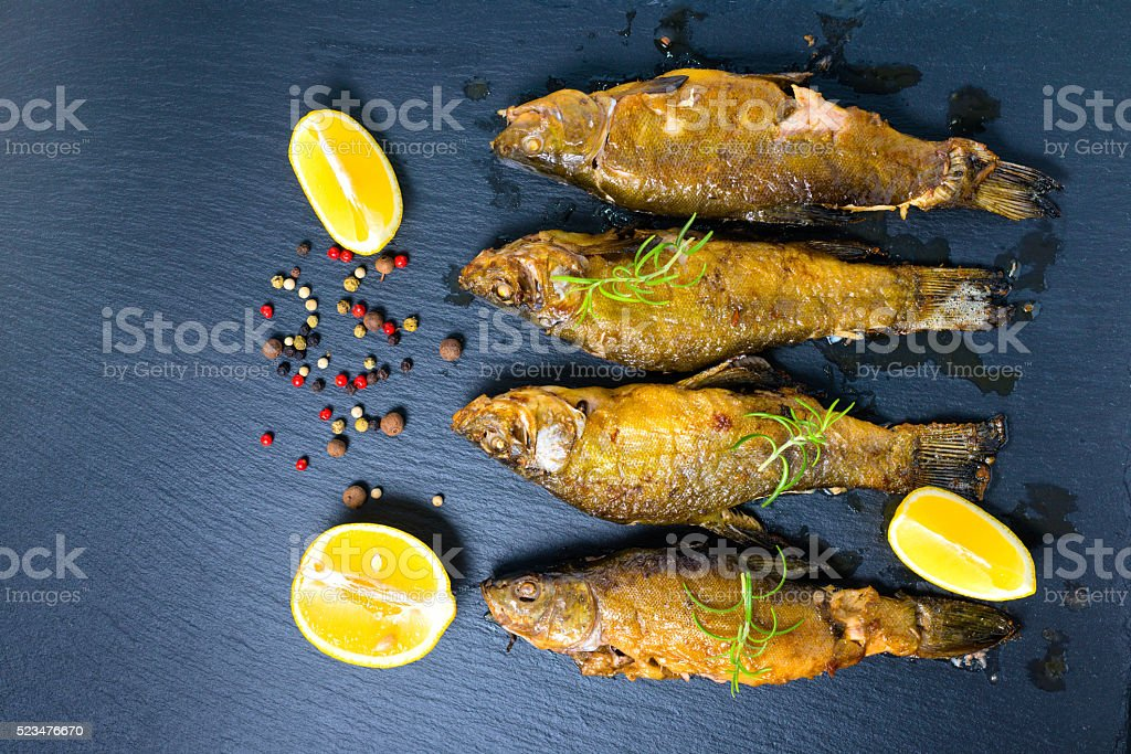 top view of fried tench fish served with aromatic rosemary, stock photo
