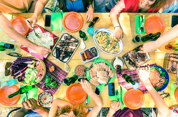 のトップビュー友人の手でのお料理をお出しするバーベキューパーティー ストックフォト
