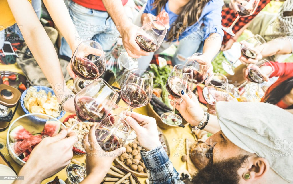 Top view of friend hands toasting red wine glass and having fun outdoor cheering at picnic winetasting - Young people enjoying summer time together at lunch bbq garden party - Youth friendship concept stock photo