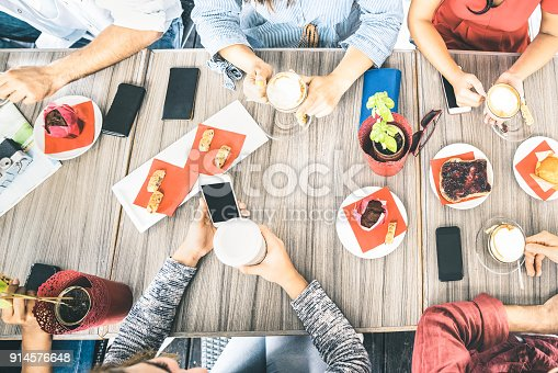 istock Top view of friends drinking cappuccino at coffee shop restaurant - People having fun together eating cakes and using mobile smart phones at cafe bar - Friendship concept on bright azure filter 914576648