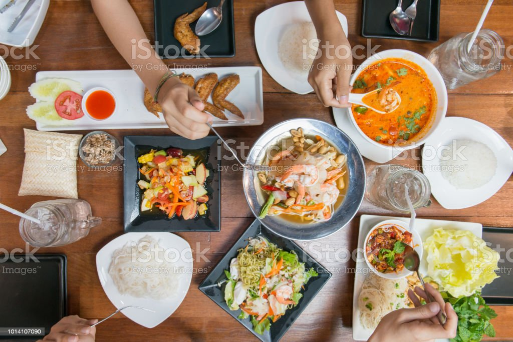 Top view of friends or family eating Thai food together on wood table. stock photo