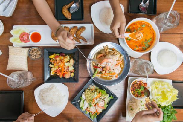 友人や家族の木のテーブルで一緒にタイ料理を食べるの平面図です。 - タイ料理 ストックフォトと画像