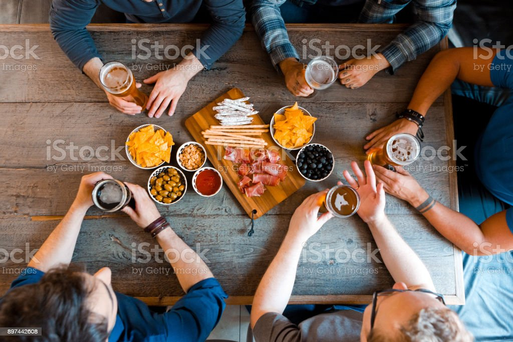 Top view of friends sitting over beer at the table in pub Top view of friends sitting at the table in the pub, drinking beer. Unrecognizable people. High angle view of table. Adult Stock Photo