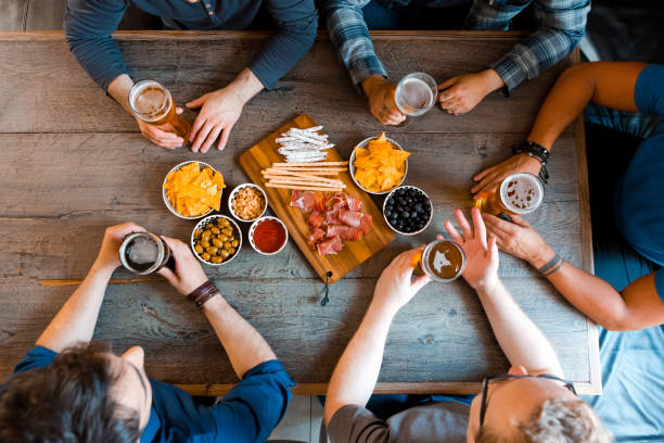 Top view of friends sitting over beer at the table in pub - foto stock