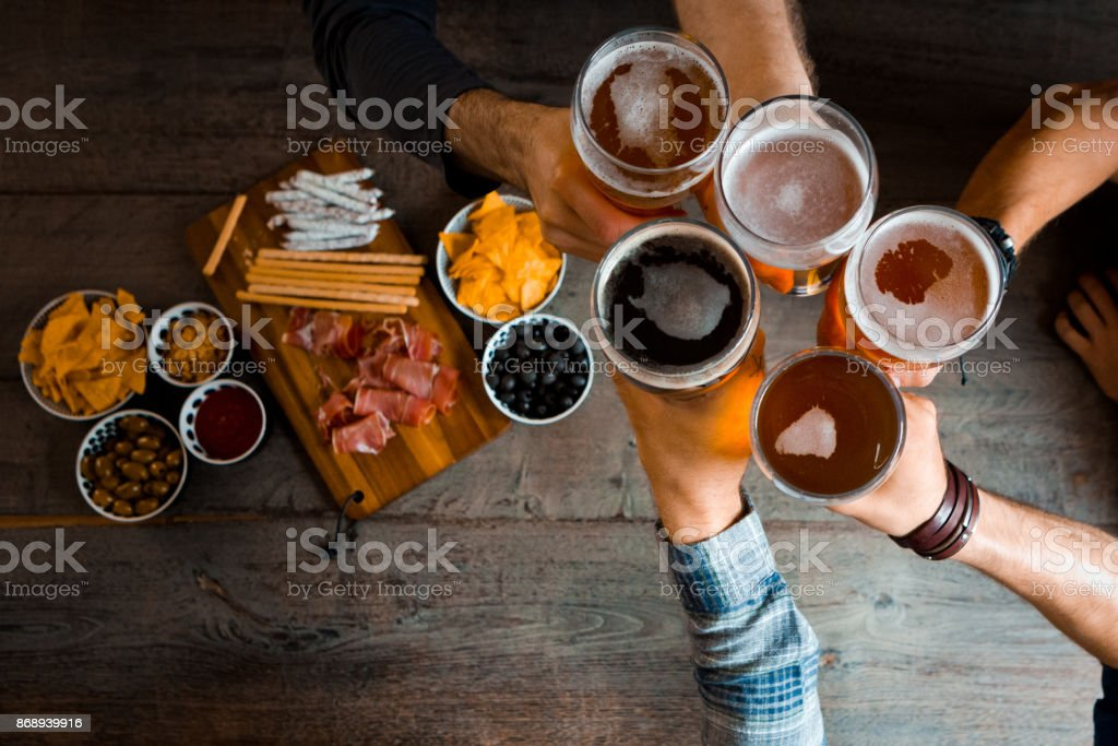 Top view of friends toasting with beer glasses in the pub